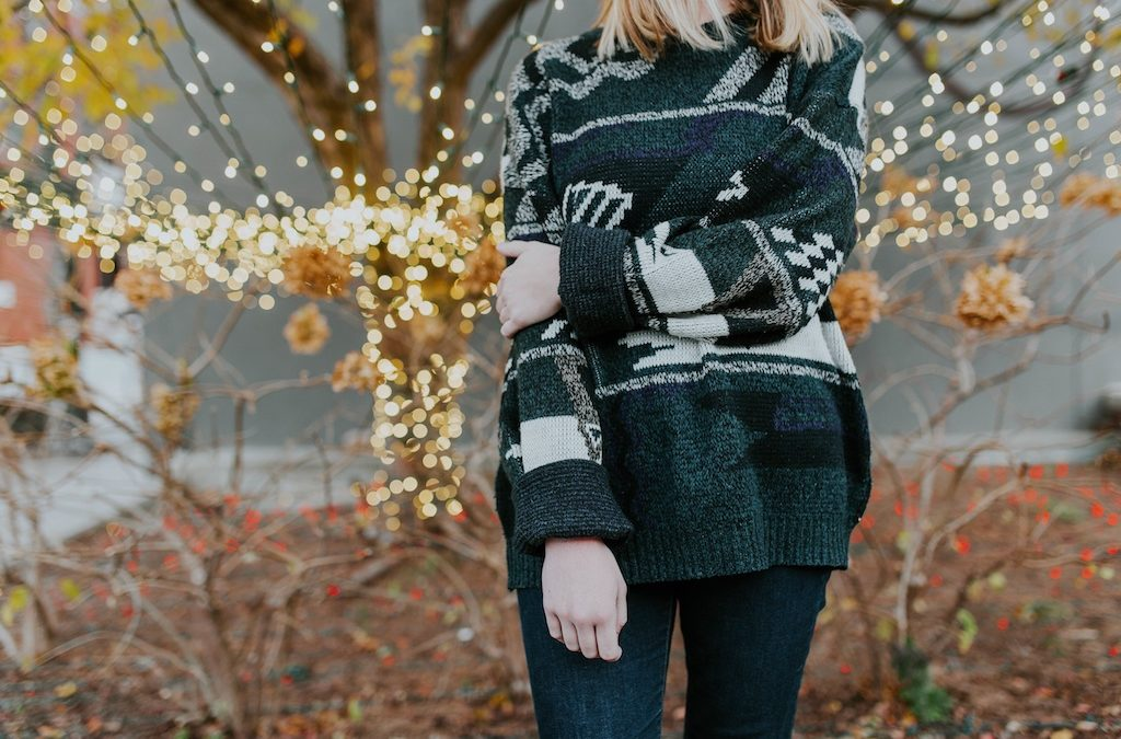 Girl wearing a holiday sweater in front of tree with lights